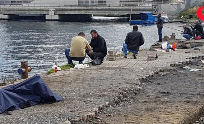 Denizden çıkarılan cesede aldırış etmeden balık tutmaya devam ettiler