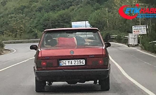 Otomobilin arka camıyla koltuğu arasında uyuyan çocuğun tehlikeli yolculuğu kamerada