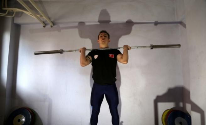 Dünya şampiyonu halterci, kapıcı dairesinde hazırlıklarını sürdürüyor